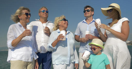 Big family drinking sea from paper cups by the sea Footage