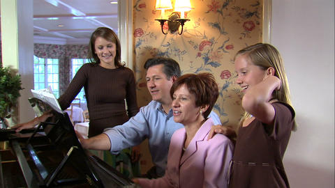 Family around a piano singing a song Live Action