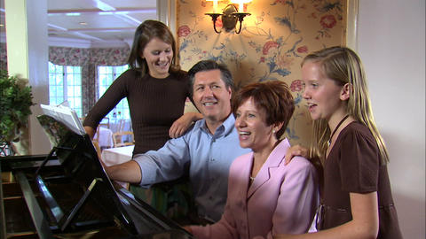 Mother playing the piano while the family sings Live Action