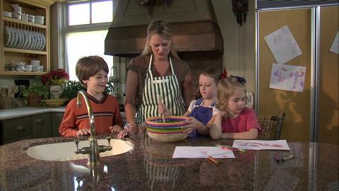 Three children helping their mother in the kitchen Footage