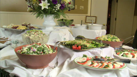 Table full of delicious looking salads and appetizers Footage