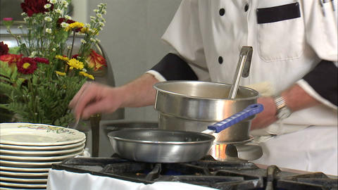 Chef adding ingredients to a frying pan Footage