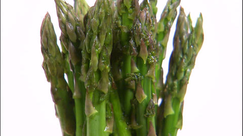 Bundle of asparagus rotating on a white screen Live Action