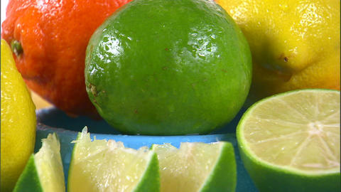 Assortment of citrus fruit rotating on a white screen Footage