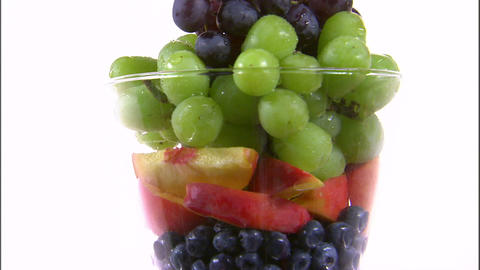 Assortment of fruit in a vase rotating on a white screen Footage