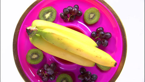 Assortment of fruit on a rotating plate on a white screen Live Action