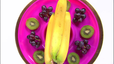 Zoom out shot of an assortment of fruit on a rotating plate Live Action