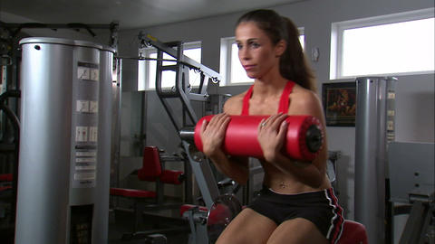 Woman doing curls on an exercise machine in a gym Footage