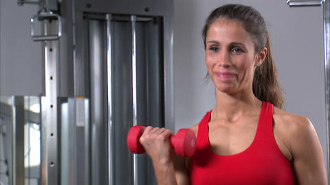 Woman doing arm curls with a pair of dumbbells Live Action