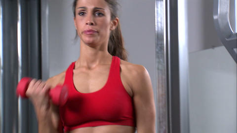 Woman doing arm curls with a pair of dumbbells in a weight room Footage