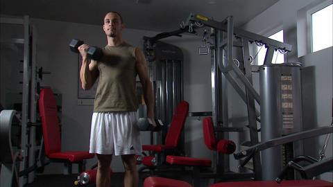Man doing arm curls with dumbbells in a weight room Footage