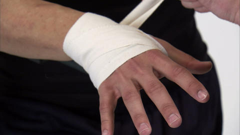 Close-up of a man's hands getting taped by a trainer Live Action