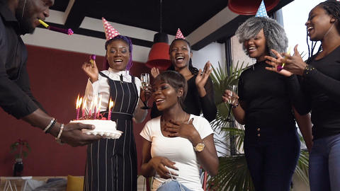 Emotional african girl on the birhday party blowing candles on the birthday cake Footage