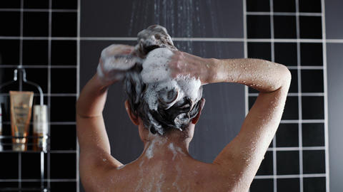 Woman washes her hair with shampoo in the shower with, hair care, ceratin mask Footage