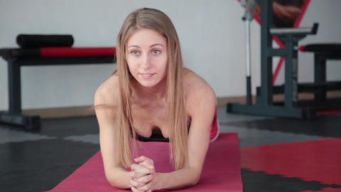Young woman doing exercise plank in gym. Girl strains muscles of abdominal press Live Action