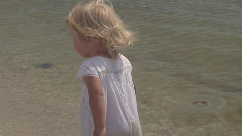 Beautiful little girl walks along the seashore. Little girl in a white dress on Live Action