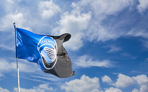 Atalanta flag waving against blue sky with white clouds フォト