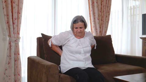 Senior woman suffering from backache at home GIF