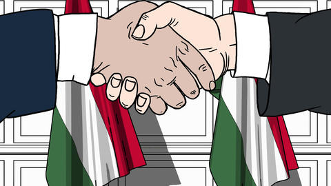 Businessmen or politicians shake hands against flags of Hungary. Official Footage