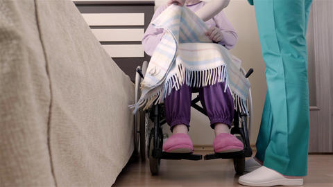 Nurse helping elder disabled woman in wheelchair to put her in bed Footage