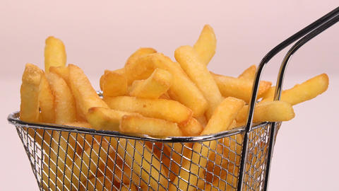 French fries in a small iron frying basket on turntable GIF