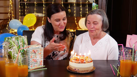 Daughter and senior mother blowing candles on birthday cake or Mothers Day party ビデオ