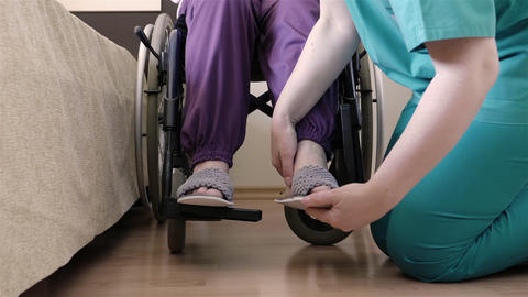 Nurse caring of elder disabled woman in wheelchair Live Action
