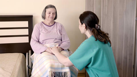 Elderly woman on wheelchair in nursing home with her care assistant Footage