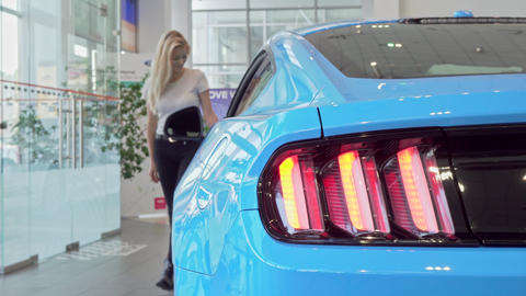 Selective focus on car lights, woman choosing automobile to buy on background ビデオ