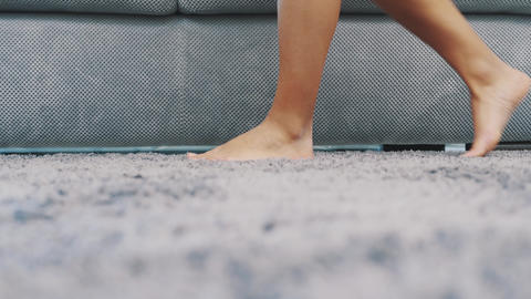 Women's legs are walking on a gray carpet that is on the floor. Fluffy carpet Live Action