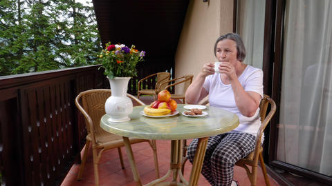 Senior woman drinking her coffee on terrace in summertime Footage