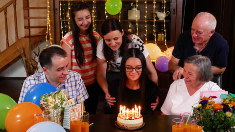 Teenage girl blowing candles on birthday cake at party with the family Footage