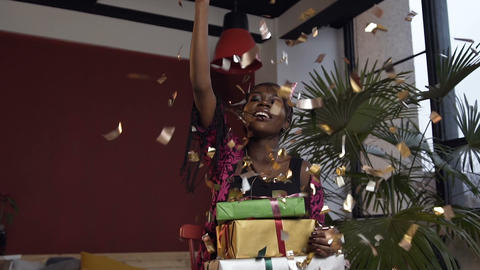 Portrait shot of happy african woman with boxes with gifts throwing gold Live Action