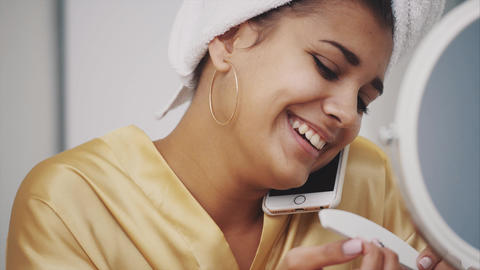 Young woman smiles. Waking up in the morning Happy girl with a towel on her head Footage