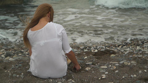 Back view of young woman sitting on the beach, playing with sand near the sea Footage