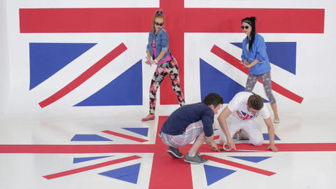 Two girls synchronically dance while two guys tape floor with british flag Live Action