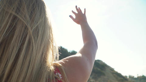 Blond girl stretched out hand to the sun. Young woman playing with sun rays with Footage