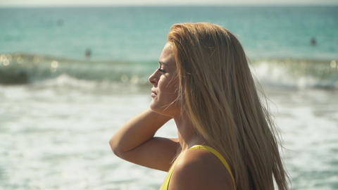 Woman with blond hair stands walking near the sea, her hair is fluttering in Live Action
