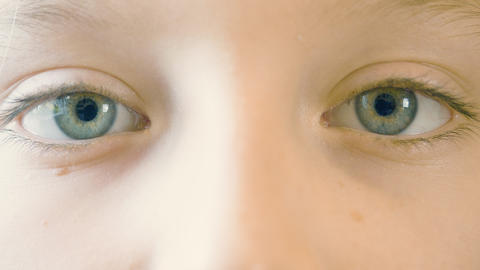 Close up motion of children eyes. Eyes of girl looking up, down, left and right Footage