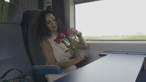 Young woman in love on train admiring roses received from her valentine love and Live Action