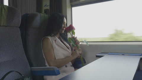 Young woman in love on train admiring roses received from... Stock Video Footage