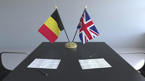 Flags of Belgium and Great Britain and papers on the table. Negotiations and Footage