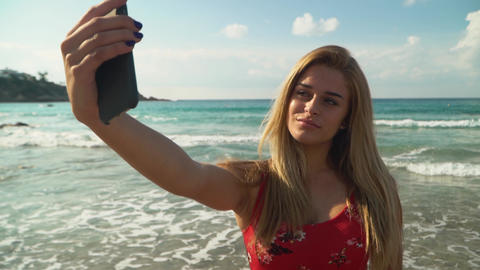 Portrait of cute young woman with blond hair taking selfie on her cellphone at Footage