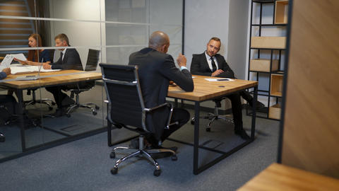 Two Diverse businessmen discussing planning talking during evening briefing at Footage