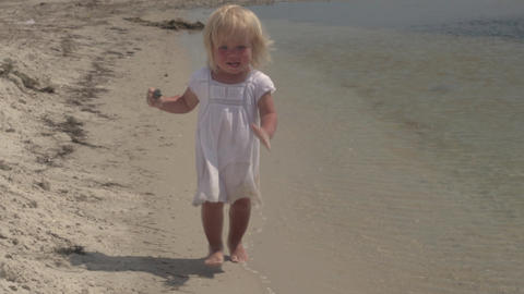 Beautiful little girl runs along the seashore. Laughing baby. Little girl in Live Action