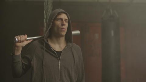 Grim looking hoodlum in hoodie holding baseball bat Footage
