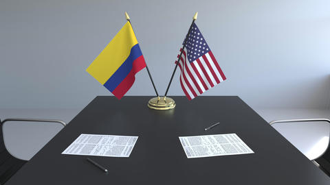 Flags of Colombia and the United States of America and papers on the table Live Action