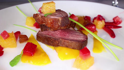 Duck breast slices on plate. Fine dining gourmet food video. Mango orange Live Action