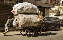 New Dehli, India, Feb 19, 2018: Man carrying massive load on bicycle Photo