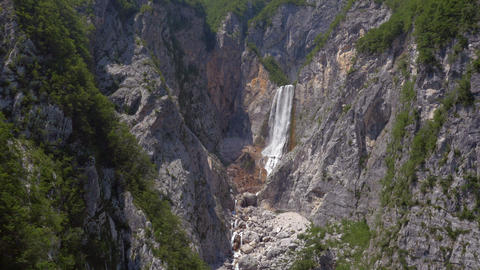 Aerial - Flying between rocky walls towards the mountain waterfall Footage
